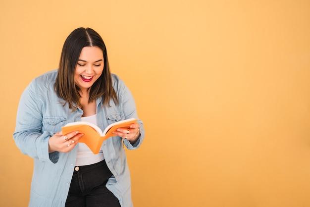 자유 시간을 즐기고 노란색 벽에 서있는 동안 책을 읽는 젊은 더하기 크기 여자의 초상화. 라이프 스타일 개념.