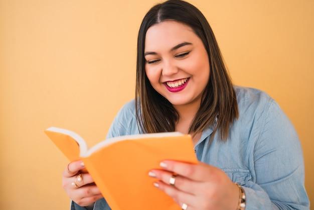Портрет молодой женщины больших размеров, наслаждающейся свободным временем и читающей книгу, стоя на желтом. концепция образа жизни.