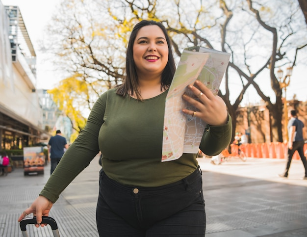 Портрет молодой женщины больших размеров, держащей карту и ищущей направления на улице на улице. концепция путешествия.