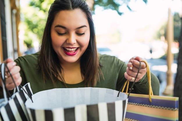 ショッピングバッグを持って、通りで屋外で興奮しているように見える若いプラスサイズの女性の肖像画。ショッピングと販売のコンセプト。