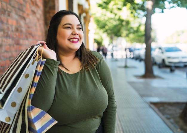 路上で屋外で買い物袋を保持している若いプラスサイズの女性の肖像画