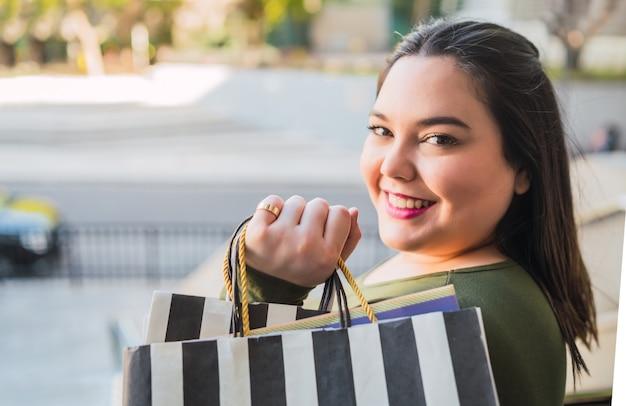 ショッピングモールで買い物をしながら買い物袋を持っている若いプラスサイズの女性の肖像画。ショッピングと販売のコンセプト。