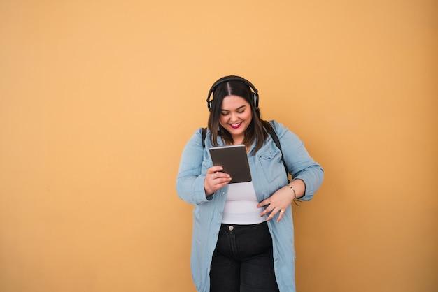 노란색 벽에 야외에서 헤드폰 및 디지털 태블릿으로 음악을 듣고 젊은 더하기 크기 여자의 초상화.
