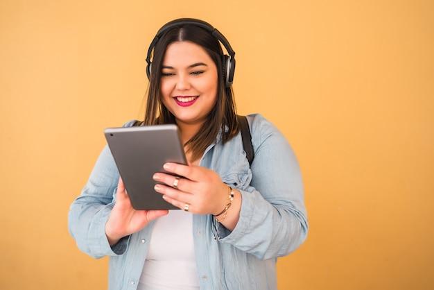 Портрет молодой женщины размера плюс, слушая музыку с наушниками и цифровым планшетом на открытом воздухе на желтом.