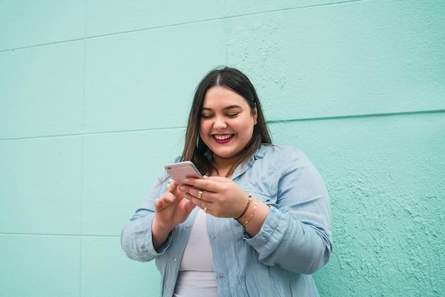 야외에서 그녀의 휴대 전화에 문자 메시지를 입력하는 동안 웃 고 젊은 더하기 크기 여자의 초상화.