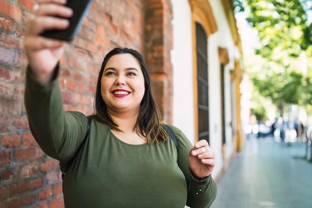 通りで屋外で彼女のmophile電話でselfiesを取っている若いプラスサイズの女性の肖像画