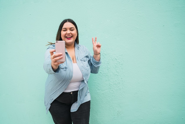屋外で彼女のmophile電話でselfiesを取っている若いプラスサイズの女性の肖像画。ライフスタイルのコンセプト。