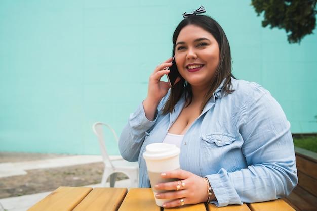 야외 커피숍에 앉아 있는 동안 전화 통화를 하는 젊은 플러스 사이즈 여성의 초상화.