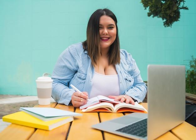 커피 숍에서 야외에서 앉아있는 동안 노트북과 책으로 공부하는 젊은 봉 제 크기 여자의 초상화.