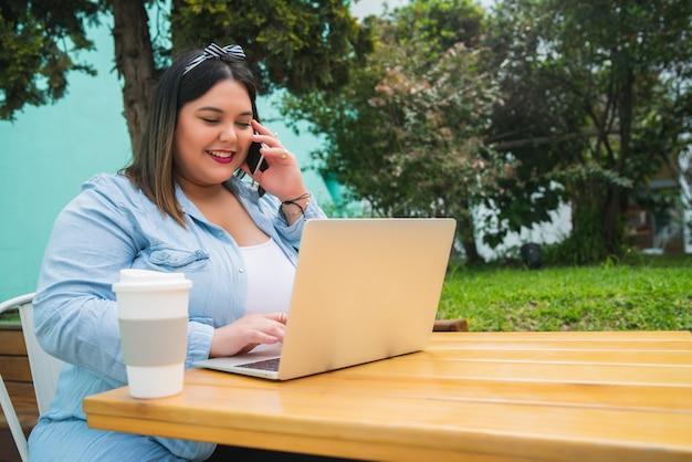 그녀의 노트북을 사용 하 고 커피 숍에서 야외에서 앉아있는 동안 전화로 얘기 젊은 봉 제 크기 여자의 초상화.