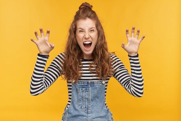 若いポジティブな生姜の女性の肖像画、正面で叫び、彼女のボーイフレンドとイチャイチャしながら彼女の爪を示しています。黄色の壁に隔離