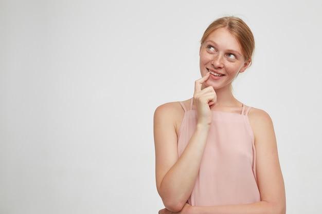 夢のように上向きに見て、白い背景の上に立っている間ピンクのシャツを着て、人差し指を下唇に保持している若いポジティブ赤毛の女性の肖像画