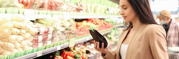가게에서 유기농 가지를 사는 긍정적인 젊은 여성의 초상화