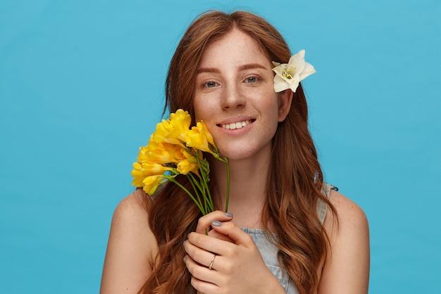 花を保持し、青い背景の上に立って、誠実な笑顔でカメラを元気に見て自然なメイクで若いポジティブな女性の肖像画