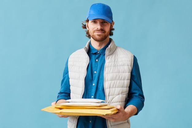 文字を保持し、青い背景にカメラを見て制服を着た若い郵便配達員の肖像画