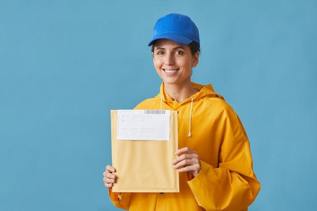 Портрет молодой почтальонки в униформе, держащей письмо и улыбающейся на синем