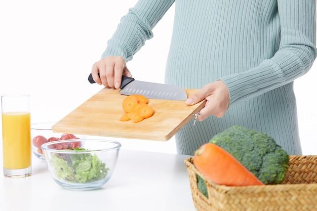 フルーツジュースとサラダを保持している若い妊婦の肖像画