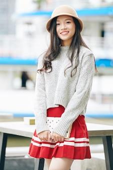 屋外に立っている本を持つ若いかわいいアジアの女子大生の肖像画