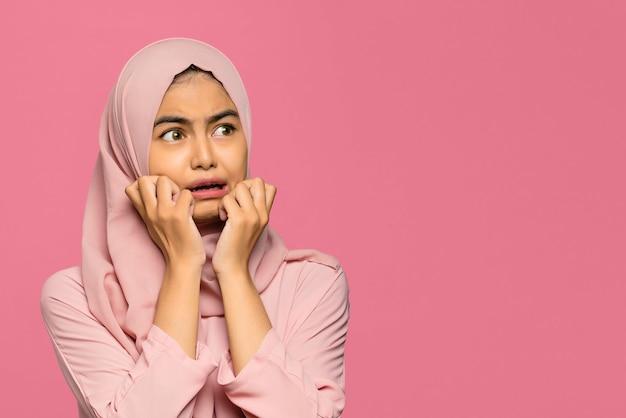 Портрет молодой красивой азиатской женщины в панике и страхе на розовом фоне