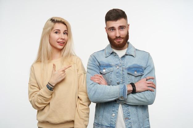 흰색에 포즈 접힌 손으로 귀여운 젊은 갈색 머리 수염 난된 남자를 긍정적으로 가리키는 베이지 색 셔츠에 젊은 예쁜 금발 여성의 초상화