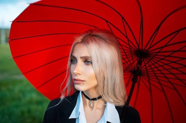 Портрет молодой довольно блондинки на фоне красного зонтика.