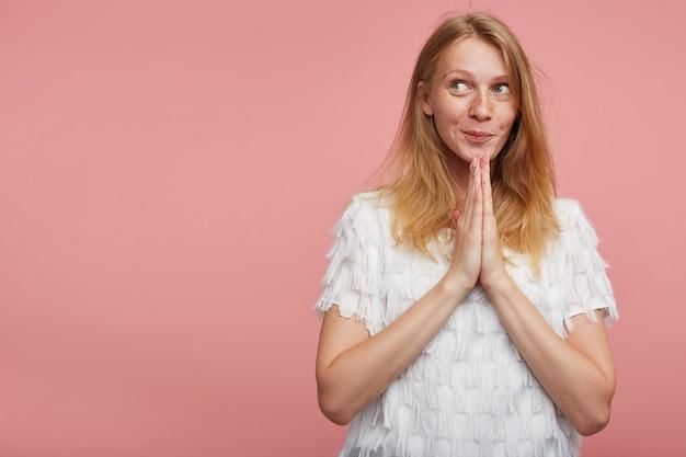 Портрет молодой довольно жизнерадостной женщины с хитрыми волосами, сложив вместе поднятые ладони и положительно смотрящей в сторону с приятной улыбкой, изолированные на розовом фоне