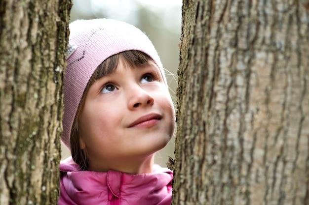 Портрет молодой красивой детской девочки в розовой куртке и кепке, стоящей между деревьями в парке
