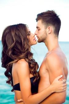 お互いに愛を込めて見ている若いかわいいカップルの肖像画。海の近くに立っている