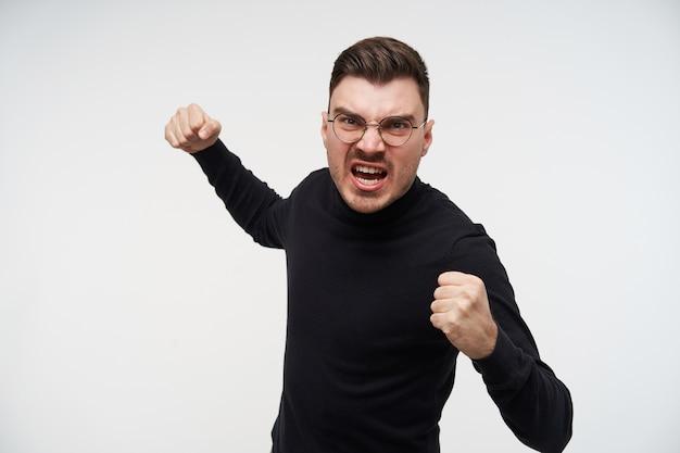 怒って眉をひそめている黒いロールネックのセーターの若いかなり暗い髪の男の肖像画