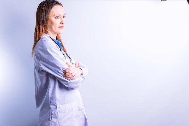 Портрет молодой красивой доктора в профиль, задумчиво выглядящий, говорящий с концепцией медицины скрещенных рук