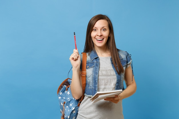 파란색 배경에 격리된 연필을 가리키고 노트북을 들고 배낭을 메고 데님 옷을 입은 젊고 흥분된 여학생의 초상화. 고등학교 대학 대학 개념의 교육입니다.
