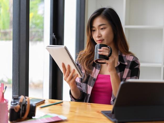 カフェでリラックスしながらコーヒーカップとデジタルタブレットを保持している若いきれいな女性の肖像画