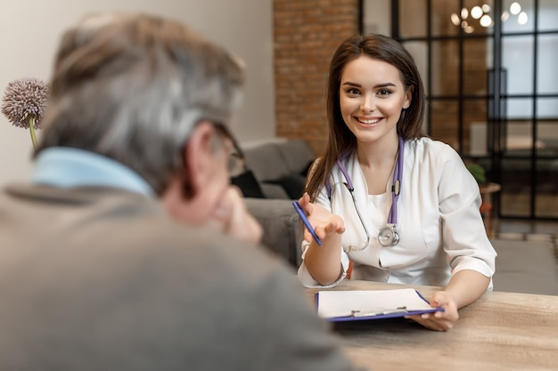若いきれいな女性の民間医師の肖像画は、自宅で年配の男性を訪問し、レシピを与えます。