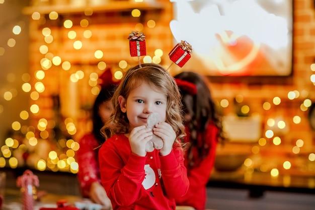 赤いクリスマスのパジャマとクリスマスの背景にキッチンで小さな白いネズミを保持しているヘッドバンドの若いかわいい女の子の肖像画。