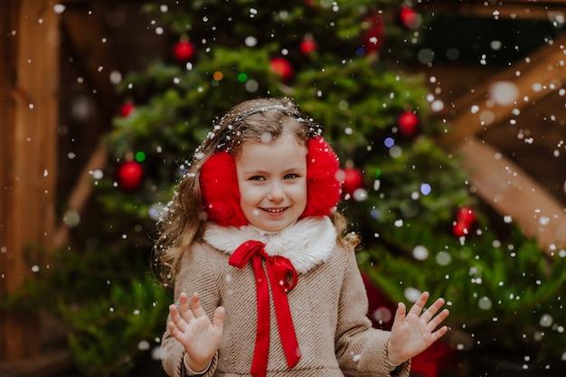 Портрет молодой красивой девушки в зимнем пальто и красных наушниках позирует на деревянной террасе