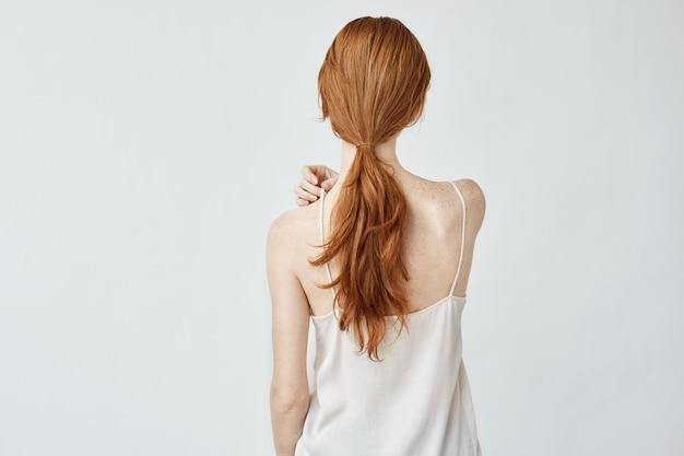 Портрет молодой красивой девушки с лисьими волосами позирует сзади