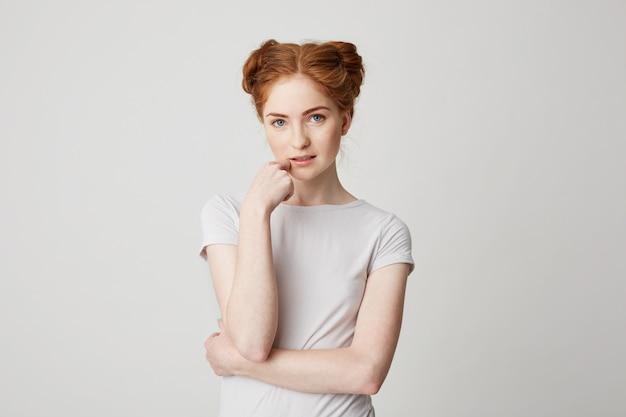 あごに触れる赤い髪の若いきれいな女の子の肖像画。