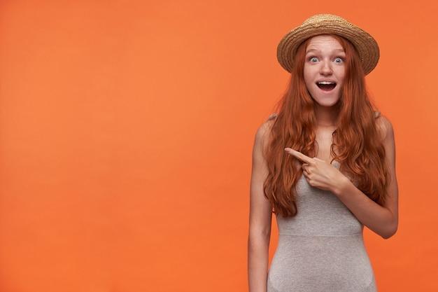 Портрет молодой красивой дамы с волнистыми рыжими волосами, стоящей на оранжевом фоне, глядя в камеру с удивленным лицом, округляя глаза с широко открытым ртом, указывая в сторону указательным пальцем