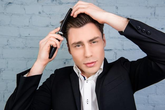 Портрет молодого красивого человека, расчесывающего волосы на стене