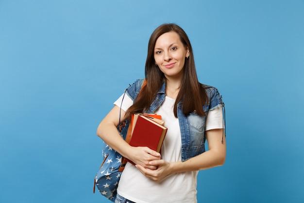 책가방을 들고 파란 배경에 고립되어 배울 준비가 된 데님 옷을 입은 젊고 유쾌한 여학생의 초상화. 고등학교 대학 대학 개념의 교육입니다.