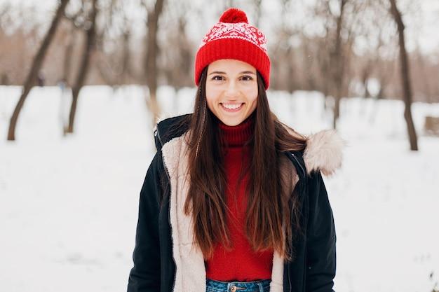 Портрет молодой довольно улыбающейся счастливой женщины в красном свитере и вязаной шапке в зимнем пальто, гуляющей в парке в снегу, теплой одежде