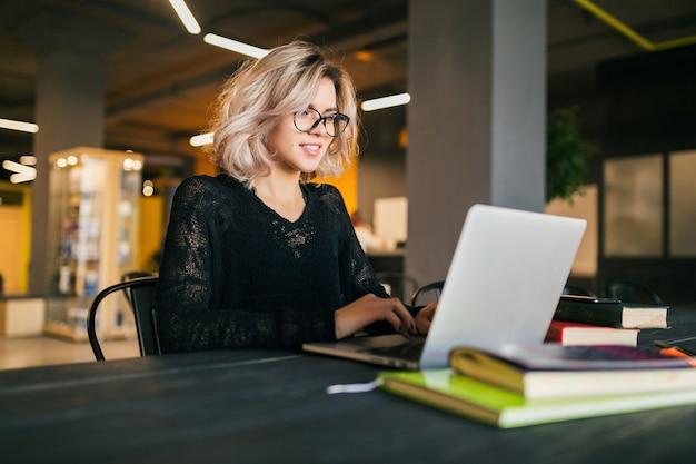 Портрет молодой довольно улыбается женщина, сидя за столом в черной рубашке, работает на ноутбуке в офисе совместной работы, в очках