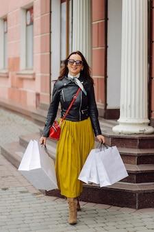 Портрет молодой довольно стильной девушки, держащей хозяйственные сумки и с нетерпением жду хорошего настроения. идеальный шоппинг.