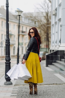 쇼핑 가방을 들고 좋은 분위기에서 기대 젊은 꽤 세련 된 여자의 초상화. 이상적인 쇼핑.