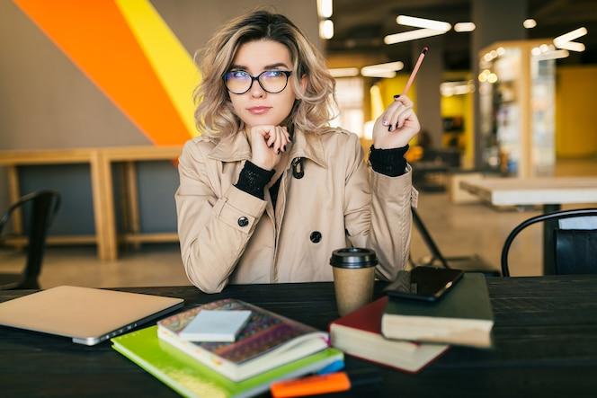 ノートパソコンで作業してトレンチコートのテーブルに座っているという考えを持つ若いきれいな女性の肖像画