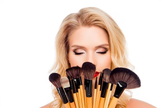 Портрет молодой красивой женщины, держащей кисти для макияжа