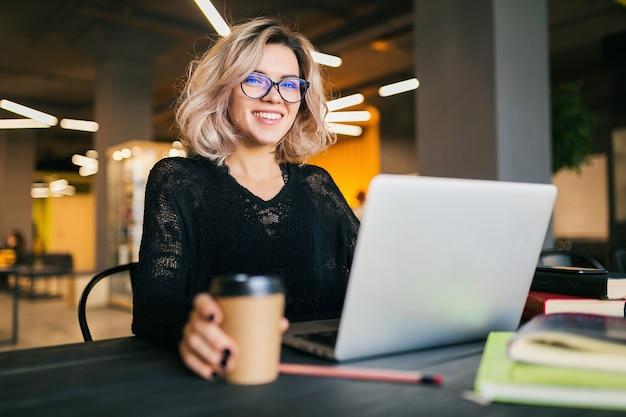 Портрет молодой красивой женщины, сидящей за столом в черной рубашке, работающей на ноутбуке в коворкинге