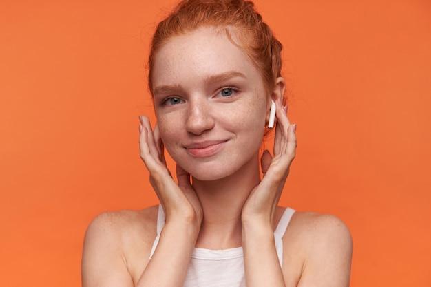 여우 같은 롤빵 헤어 스타일을 입고 이어폰에 손을 잡고 카메라에 유쾌하게 웃고, 캐주얼 옷을 입고 오렌지 배경 위에 고립 된 젊은 예쁜 여자의 초상화