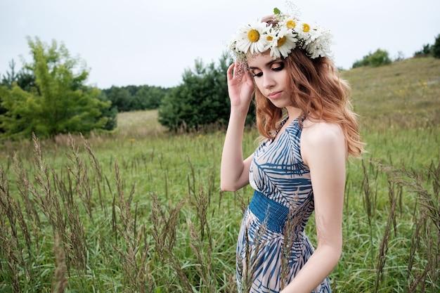 頭にカモミールの花のサークレットを持つ若いきれいな女性の肖像画