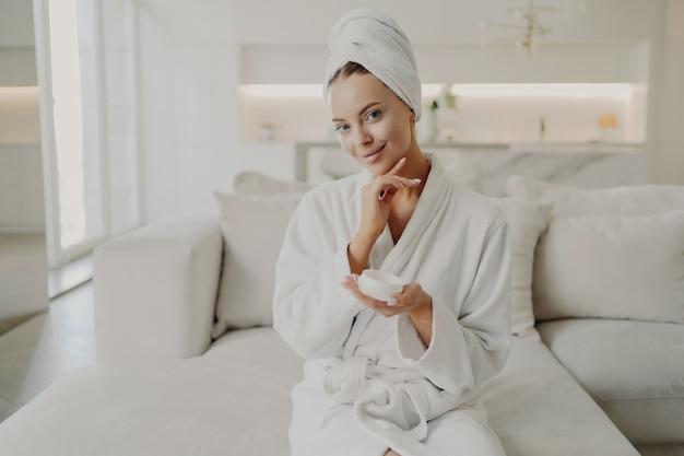 Портрет молодой красивой женщины в белом халате и полотенце на голове, держащей косметический крем, касающейся ее мягкой здоровой кожи лица и улыбающейся во время отдыха на диване в уютной квартире